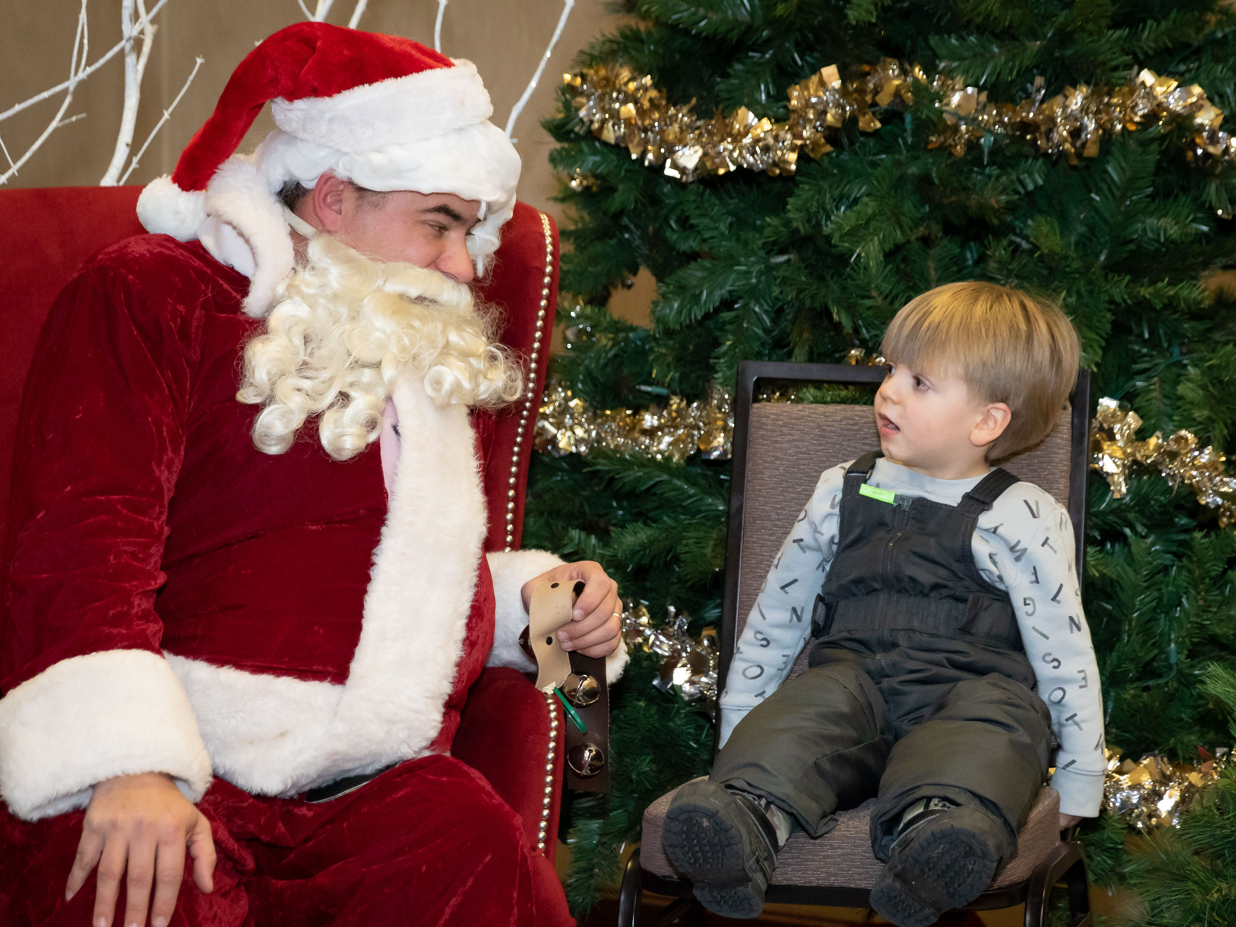 A young boy talks with Santa Claus at the Holiday Inn after the Main Street Holiday Parade on Thursday, Nov. 15, 2018, in downtown Marshfield.