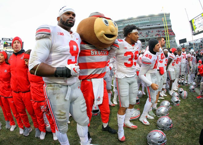 Brutus Buckeye and the players celebrate Ohio State's 26-6 victory at Michigan State.