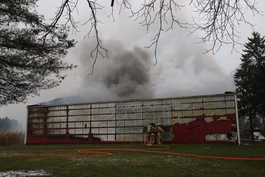 Firefighters spray water into a burning barn Friday evening.