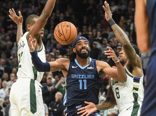 Grizzlies guard Mike Conley (11) battles for a loose ball between Bucks forward Khris Middleton (22) and guard Eric Bledsoe (6) in the fourth quarter Nov. 14, 2018, at Fiserv Center.