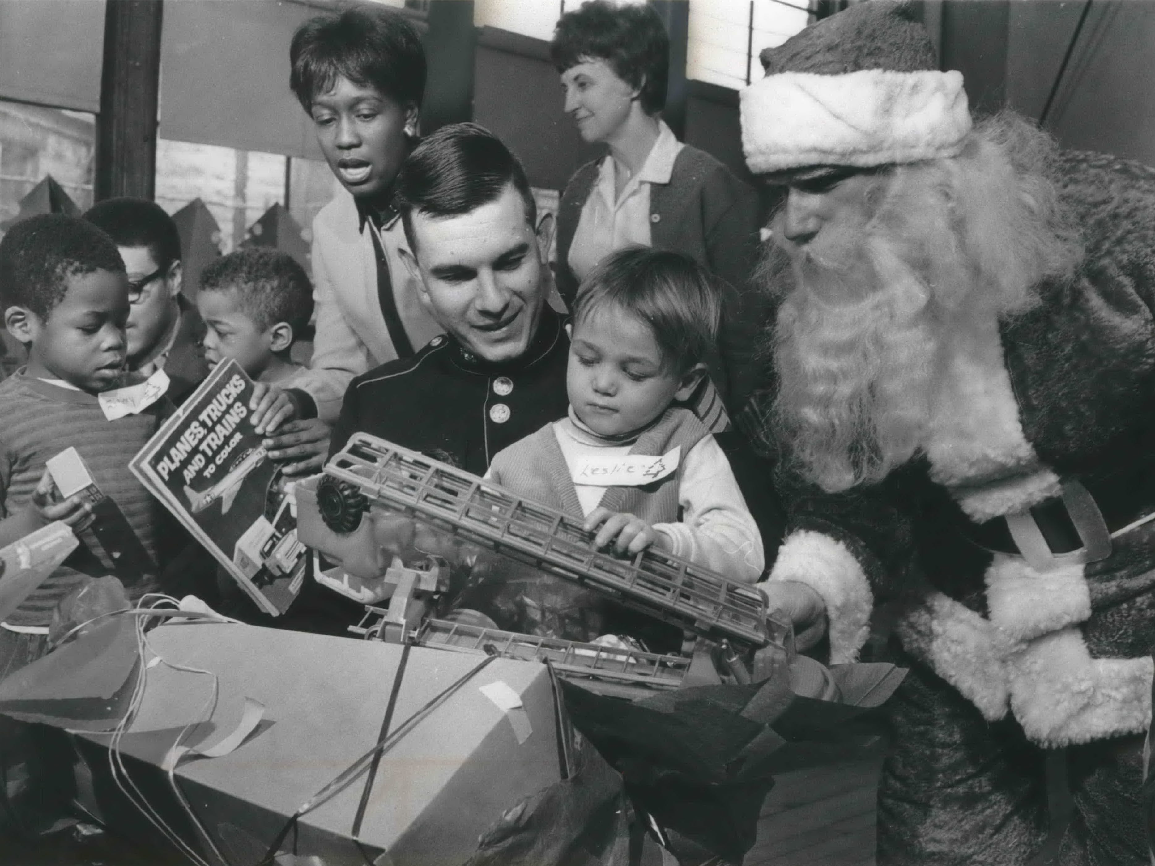 Youngsters in the Head Start program at St. Michael School, 2433 W. Cherry St., are visited by Santa and receive some Christmas presents Dec. 19, 1968, courtesy of the 96th Rifle Company of the Marine Corps Reserve. Two members of the reserve, Sgt. John Seitz and Lance Cpl. Dennis Jarentowski (dressed as Santa), helped the children open their presents. This photo was published in the Dec. 20, 1968, Milwaukee Journal.