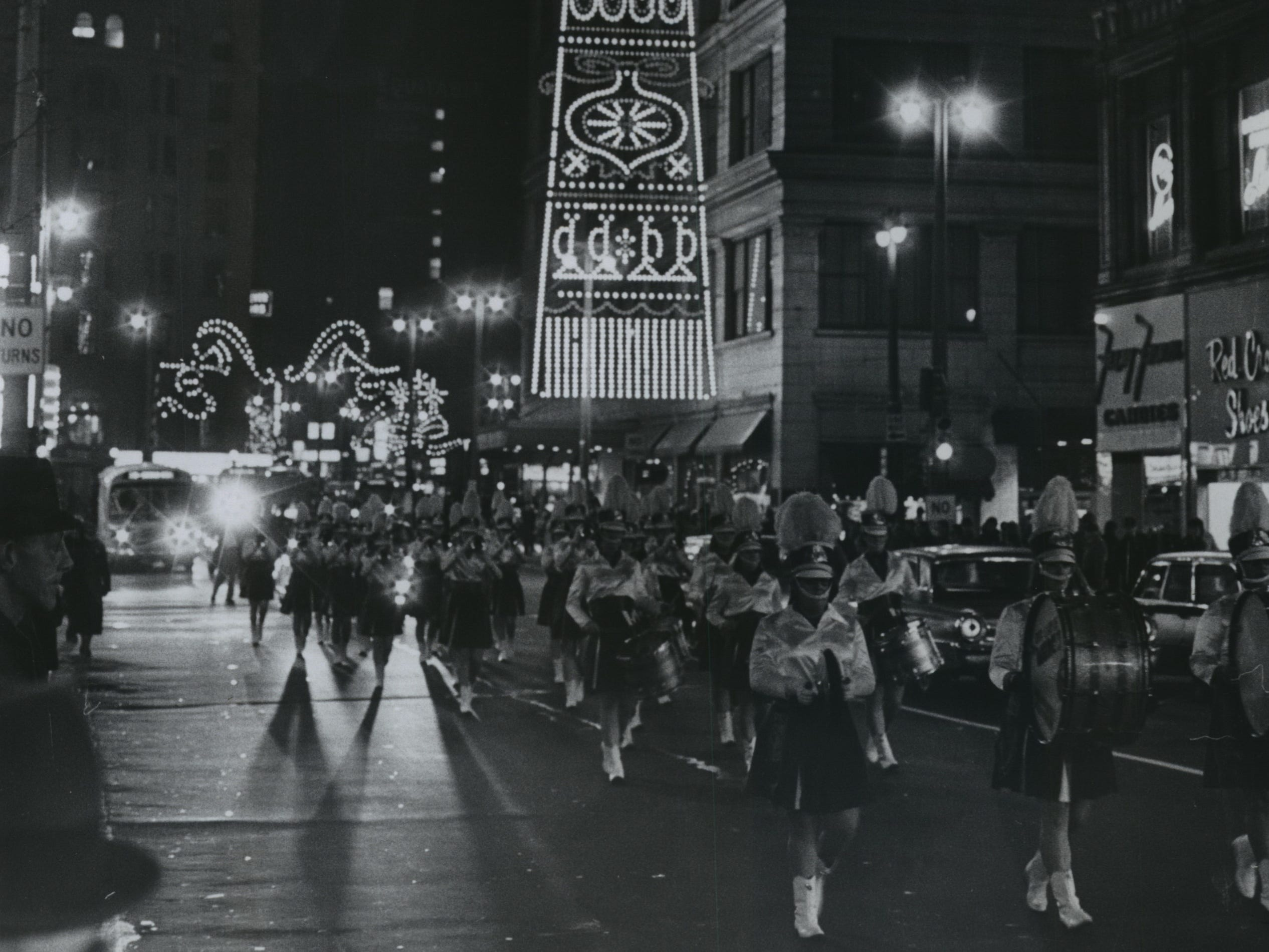 "The marching unit from Our Lady of Mercy High School parade down Wisconsin Avenue as part of Milwaukee's official opening of the Christmas ""season of lights"" along downtown streets on Nov. 22, 1968. Shopping centers and department stores across the city lighted their decorations signaling the start of the Christmas shopping season."