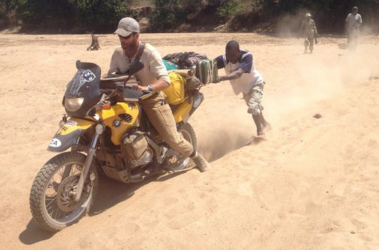 Andrew Councill, founder of Uuzilo, a motorcycle therapy program in Africa, gets a push out of the sand where the dirt road was nearly impassable.