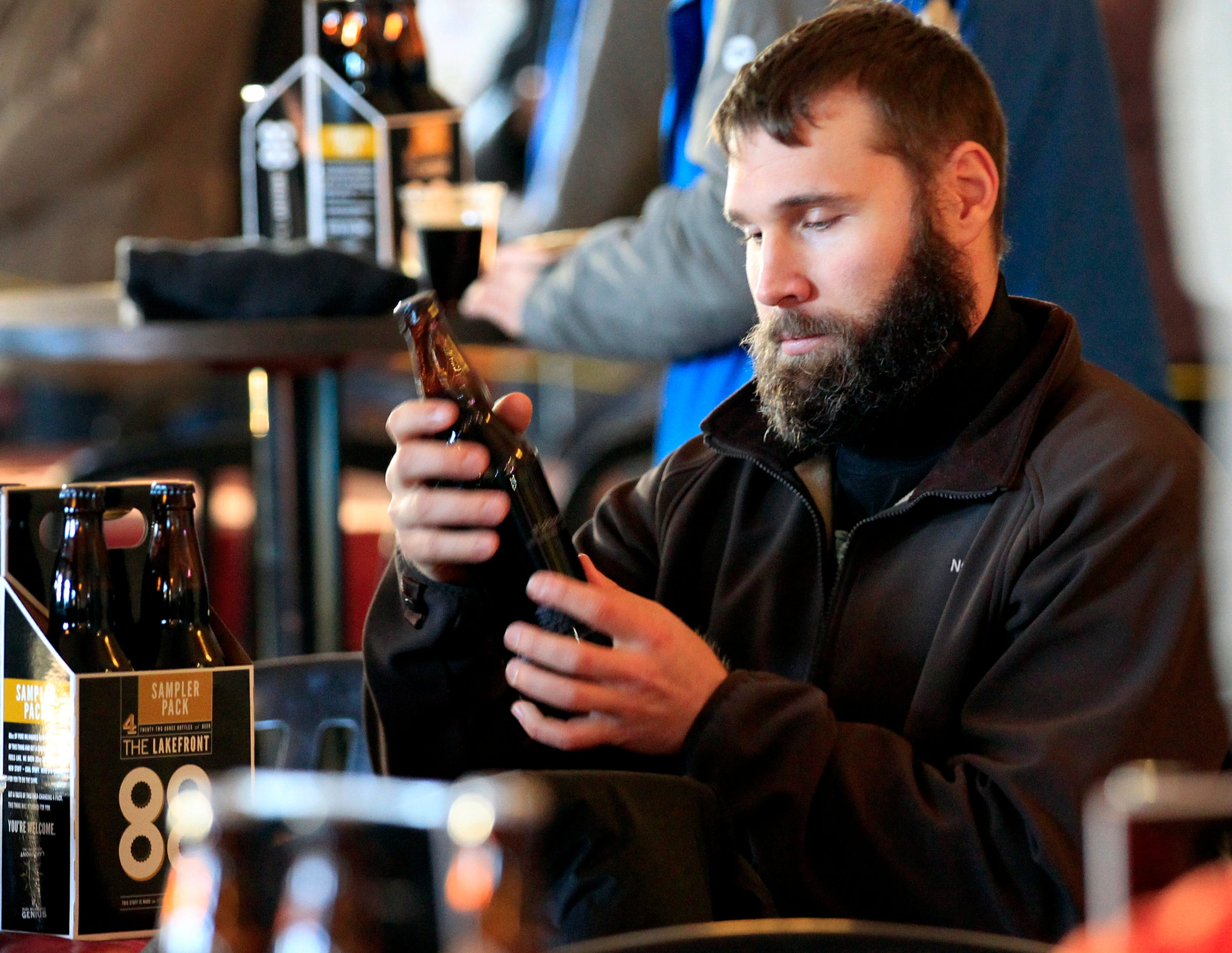 Nick Mueller of East Troy looks at a bottle of Black Friday ale during the second annual Black Friday event at Lakefront Brewery in 2013. Since then the idea has expanded to many other breweries around Milwaukee.
