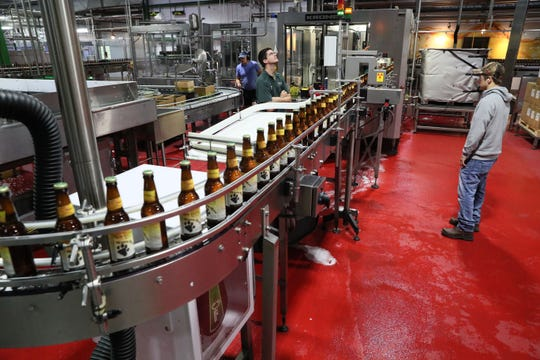 Brewery workers monitor the bottling line as it starts up.