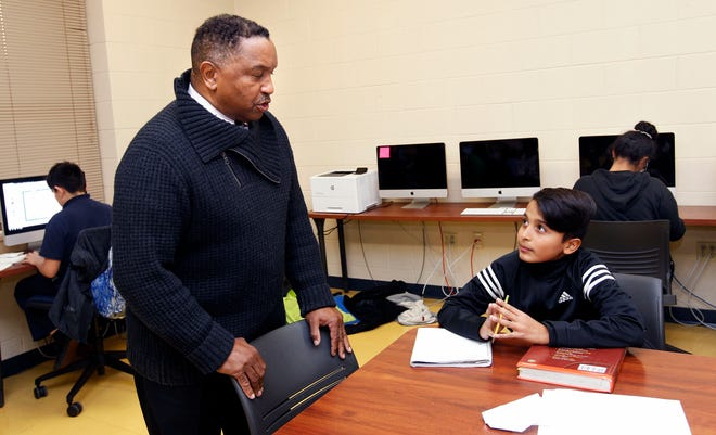 Journey House Deputy Director Charles Brown (left) talks with Rolando Contreras, 11, in one of the academic enrichment programs after school on Thursday at 2110 West Scott St., Milwaukee. Contreras also plays football at the facility.