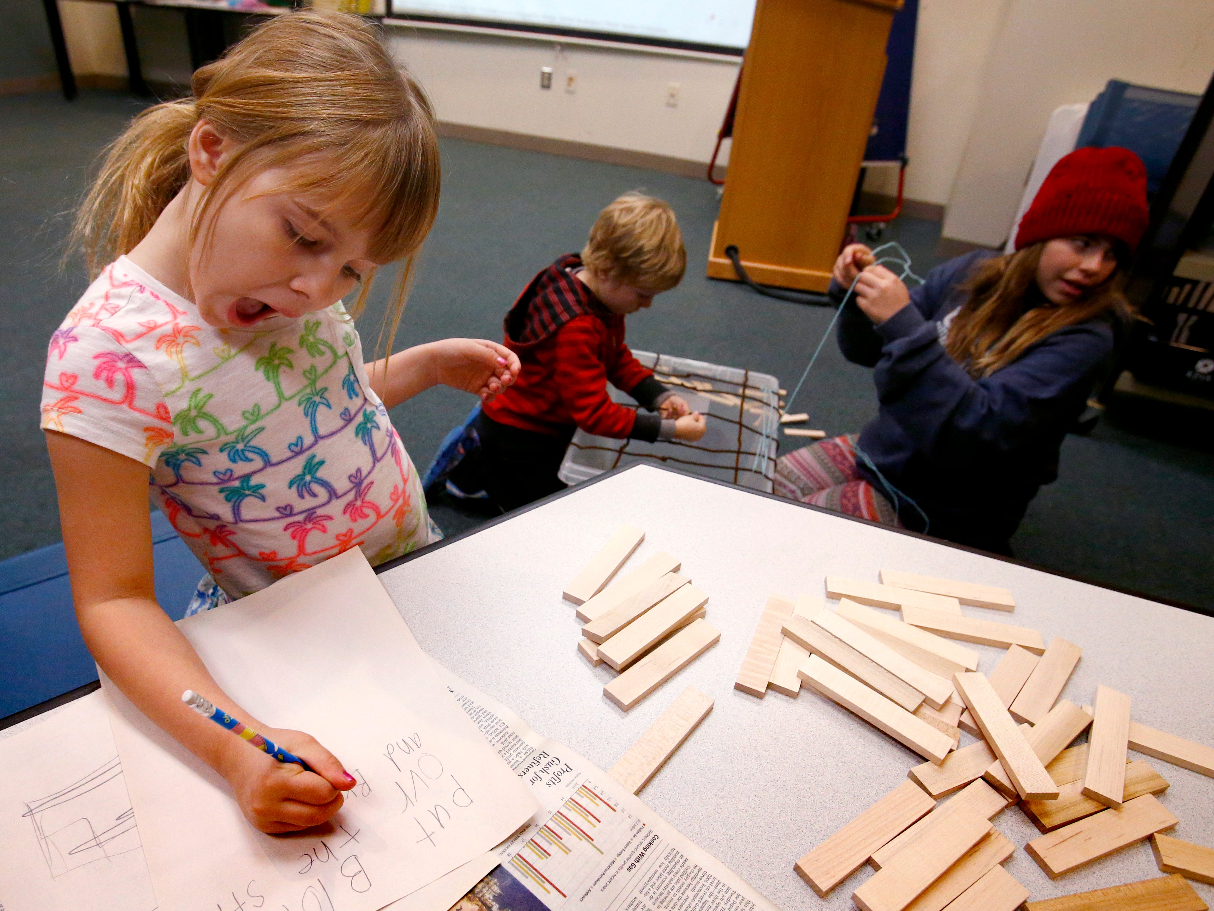 Campbell Young works on a design for a bridge that she and siblings Rhett and Adeline would build using newspaper, yard and pipe cleaners to span a tub during a STEAM - science, technology, engineering, art and math - program at the Menomonee Falls Library on Nov. 14.