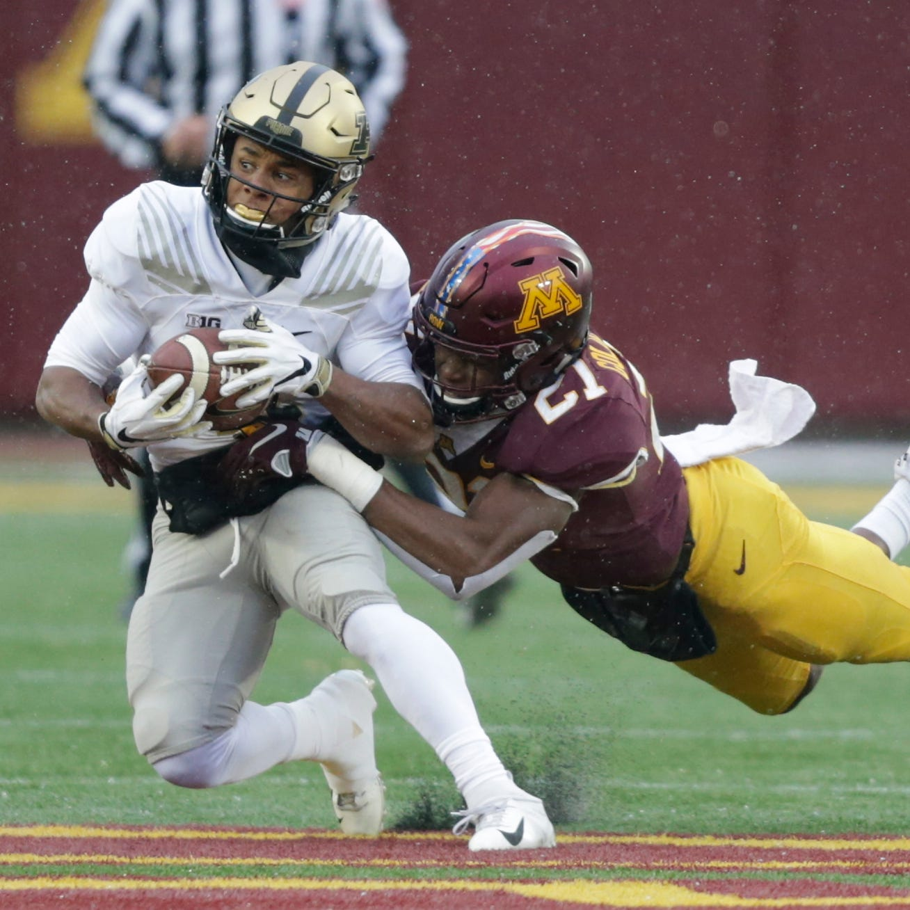 Purdue running back D.J. Knox (1) is tackled by...