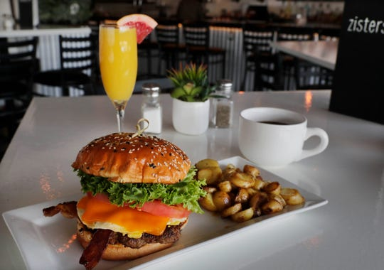 A breakfast burger with a breakfast potatoes, a cup of strong coffee and grapefruit mimosa make a fine brunch at Zisters.