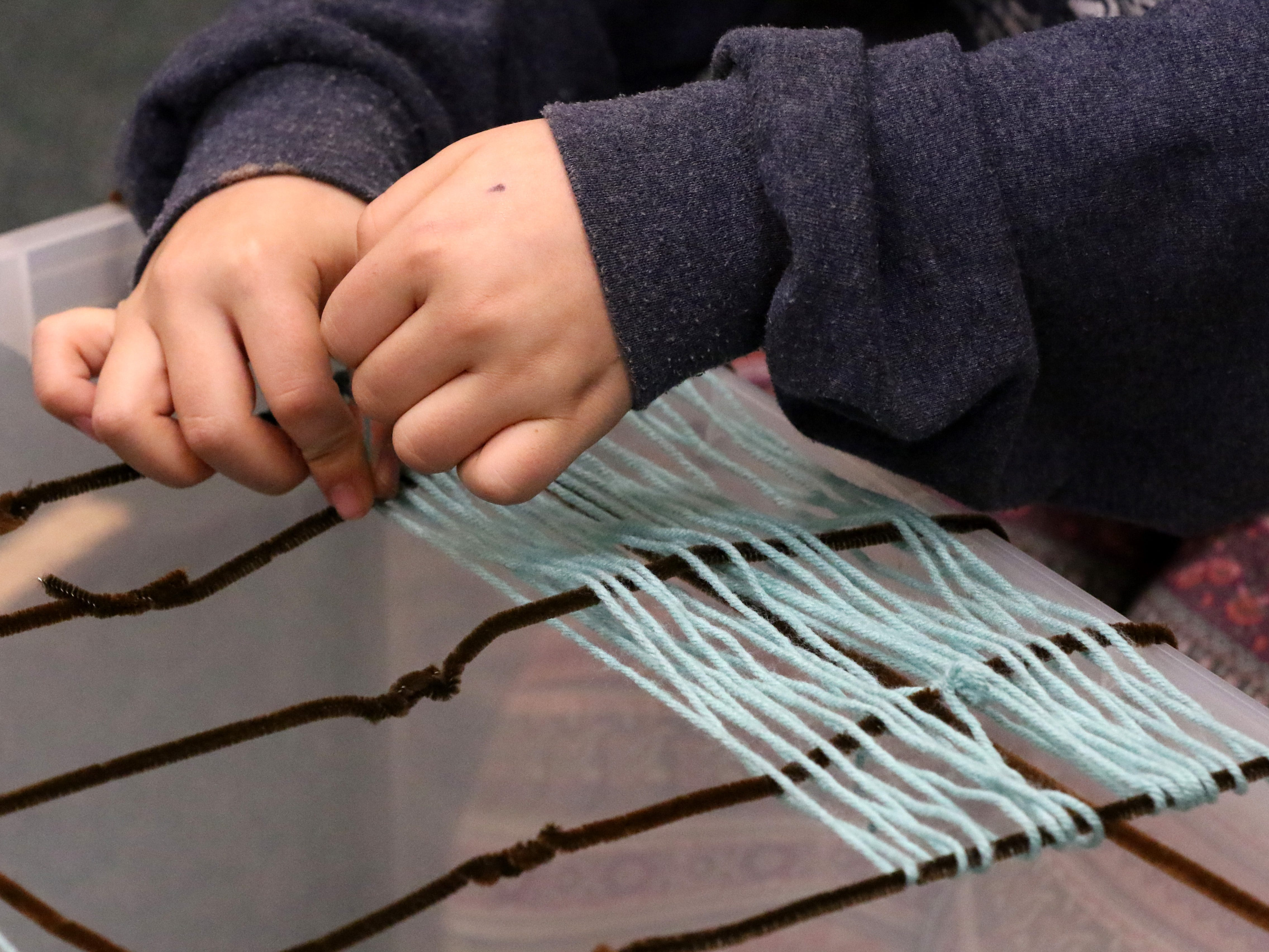 Adeline Young weaves a yarn deck between pipe cleaner supports for a bridge to span a tub during a STEAM - science, technology, engineering, art and math - program at the Menomonee Falls Library on Nov. 14.