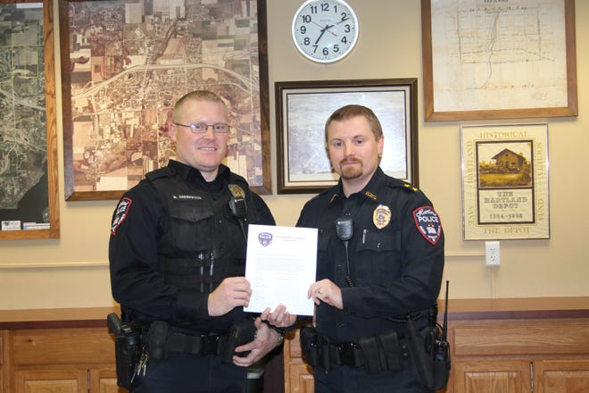 Hartland Police Officer Nick Greenwood (left) receives a lifesaving pin from Police Chief Torin Misko for his fast actions that ultimately saved a man's life.
