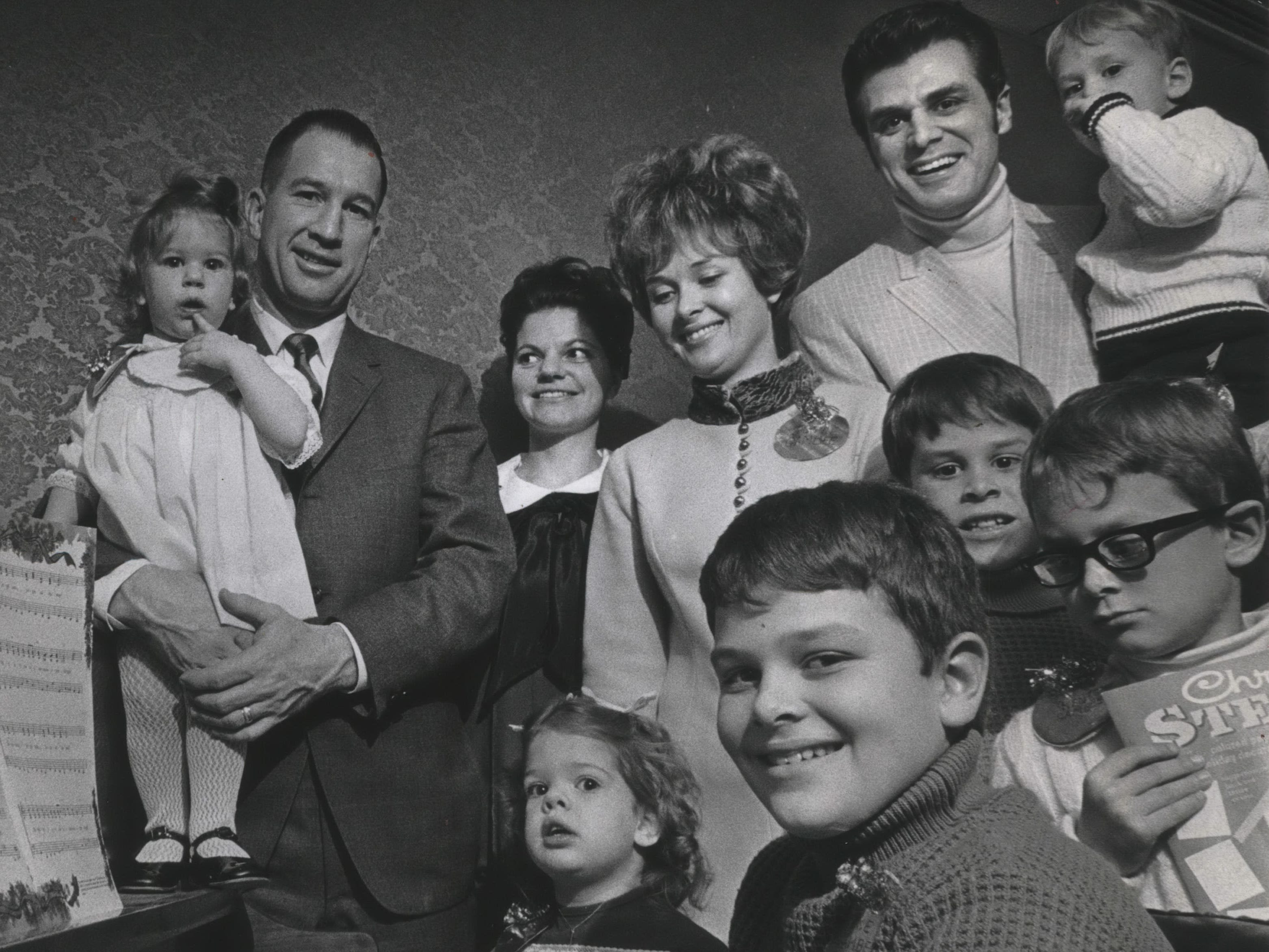 Milwaukee Bucks Coach Larry Costello and Bucks forward Dave Gambee and their families gather around the piano as Milwaukee's new NBA team holds its Christmas party at the Holiday inn Central on Dec. 15, 1968. Shown, from left: (rear) Pamela Costello; Coach Costello; Barbara Costello;  Joyce Gambee, Dave Gambee, and Brad Gambee; (front) Lesley Costello; Mike Gambee; Greg Gambee; and Kent Gambee. The party was held early because of the Bucks' tight schedule. The photo was published in the Dec. 17, 1968, Milwaukee Journal.