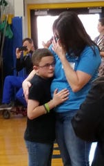 Dyson (left) gets a hug from his mother, Tessi, after learning his wish for a trip to Lego Land had been granted by the Make-A-Wish Foundation.