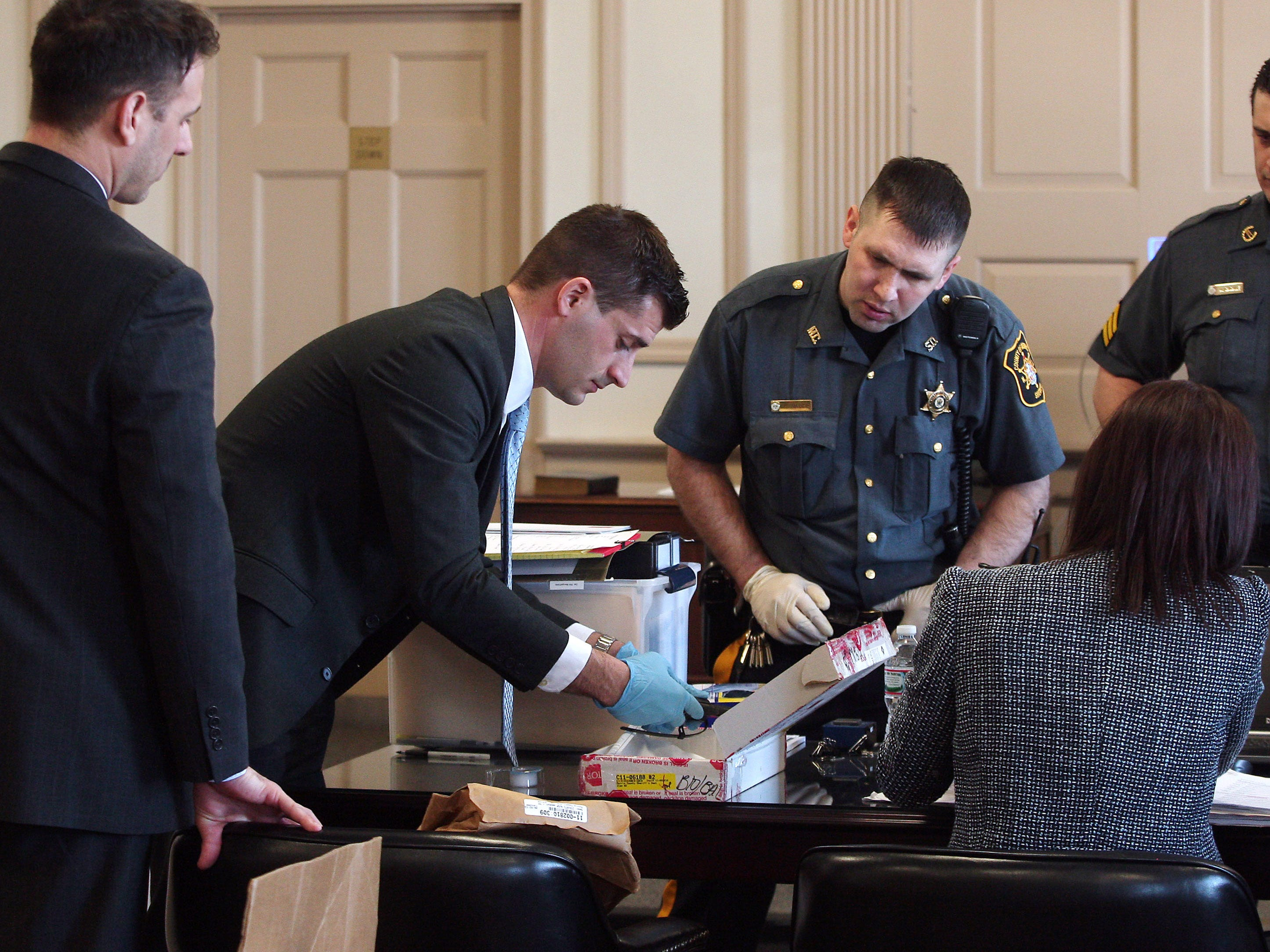 Assistant Prosecutor Matthew Troiano takes a look at one of three guns found at the residence of Antionette Stephen. Stephen pleaded guilty to murder last year and is expected to testify against Kashif Parvaiz in his murder trial, accused of killing his wife Nazish Noorani in August 2011.  February 11, 2015. Morristown, N.J. Bob Karp/Staff Photographer.