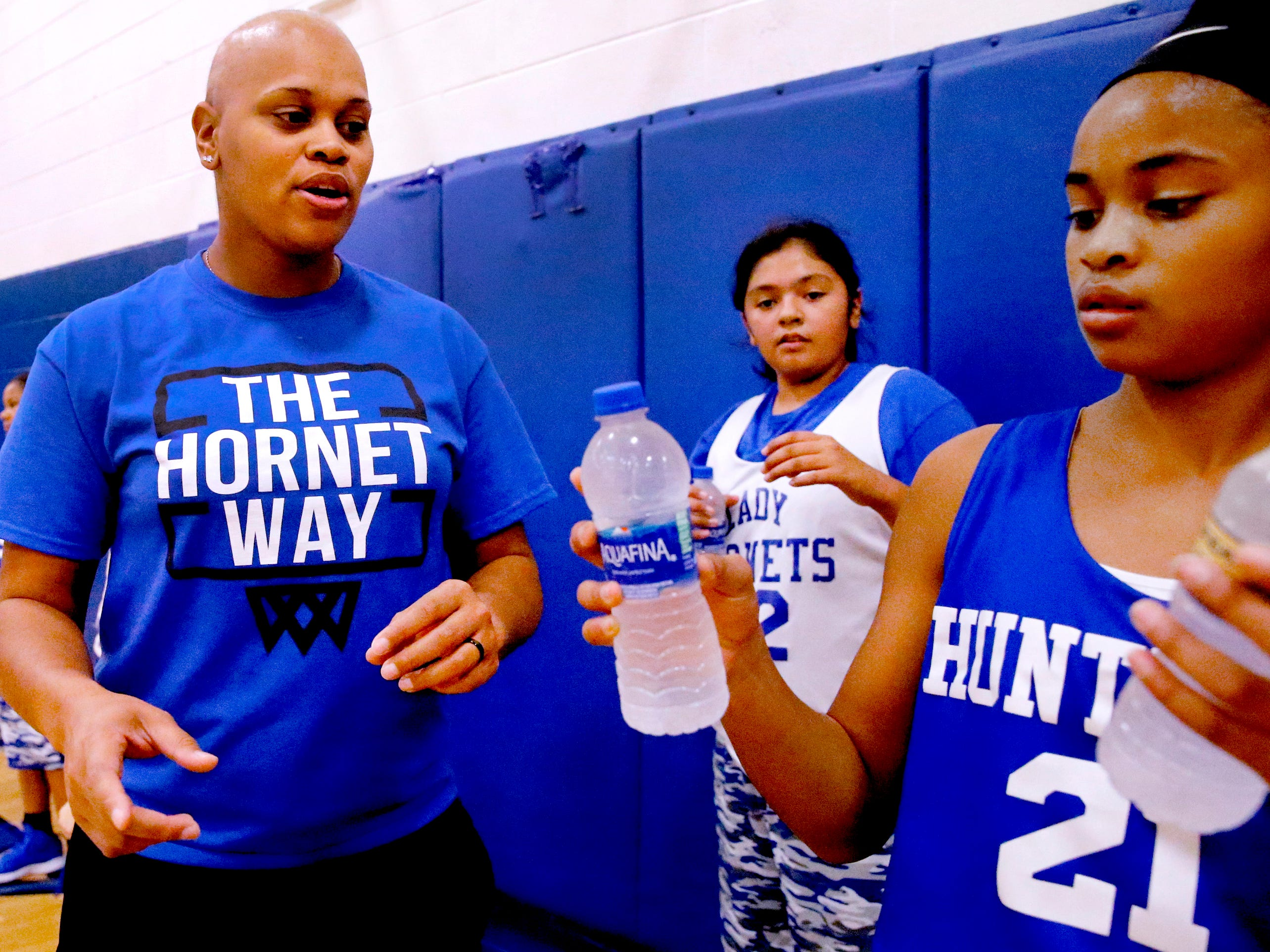 Coach Tia Stovall gets her daughter and player TaTianna Stovall to distribute water during her middle school practice on Tuesday, Nov. 13, 2018.