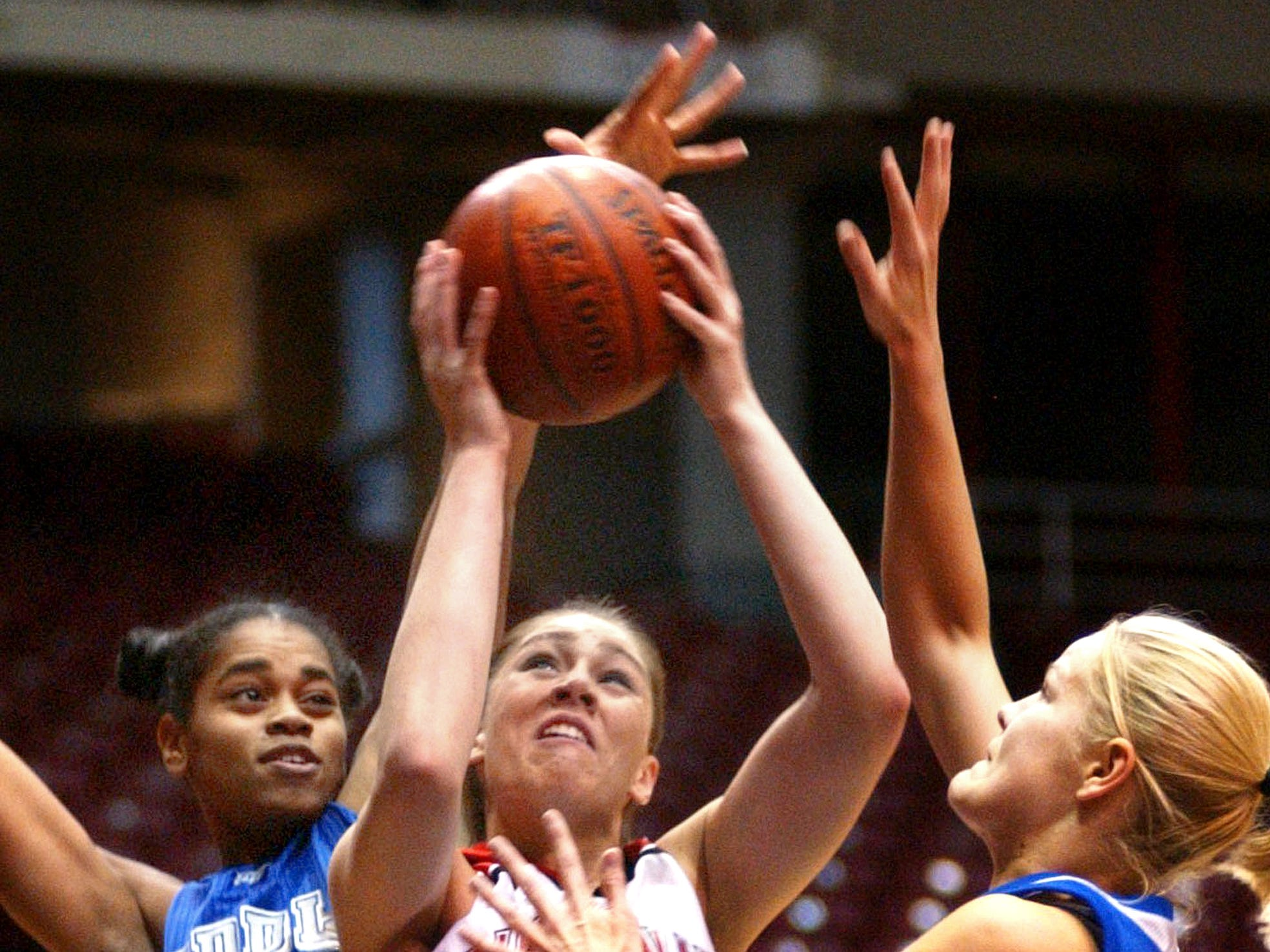 Cincinnati's Debbie Merrill, center, tries to shoot between Middle Tennessee's Tia Stovall, left, and Mia Parviainen during the first half in Cincinnati on Saturday, Nov. 30, 2002.