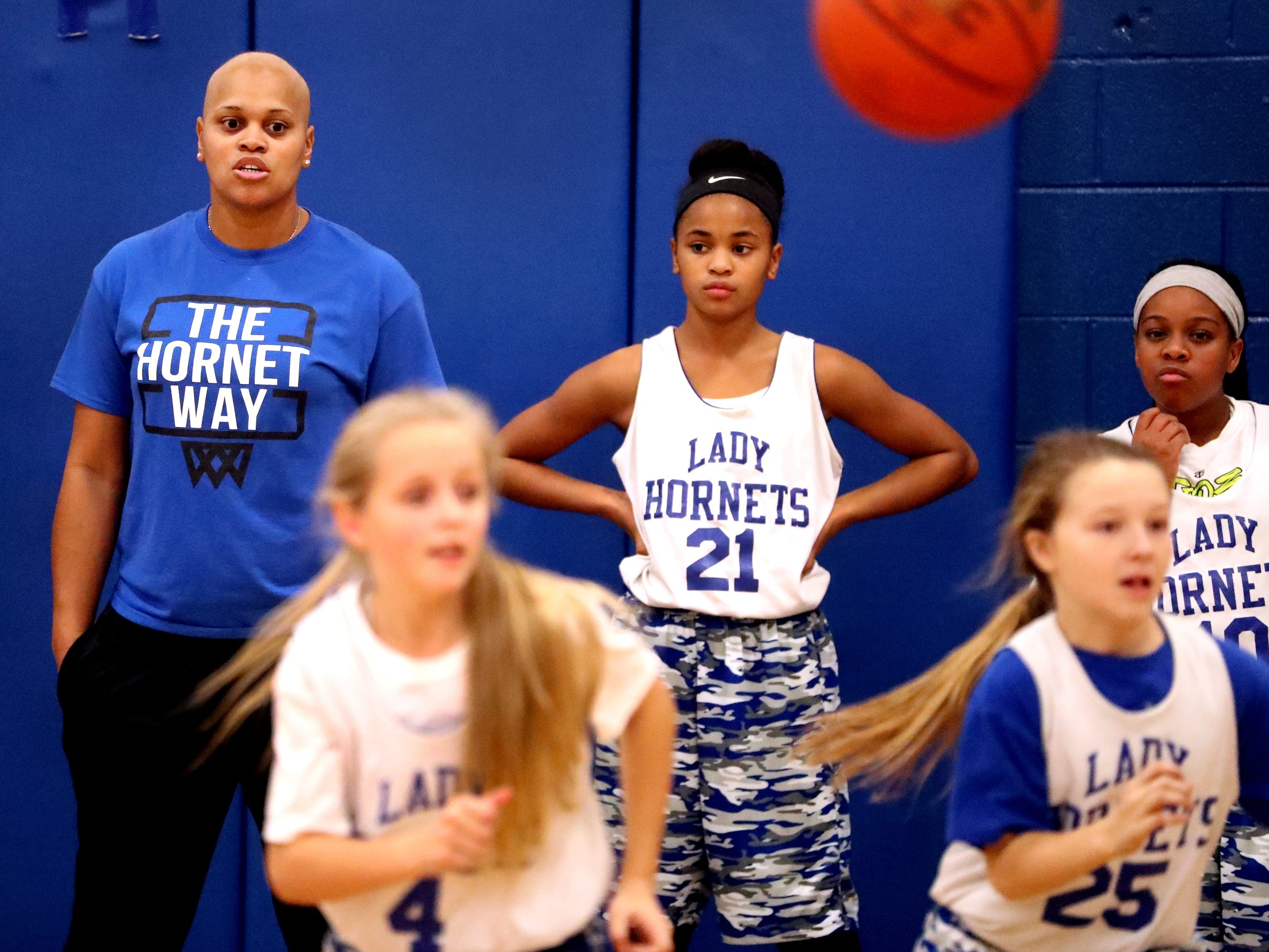 Coach Tia Stovall stands next to her daughter TaTianna during practice as Stovall (21) as Jacey Riley (4) and Marley Phillips run through a drills on Tuesday, Nov. 13, 2018.