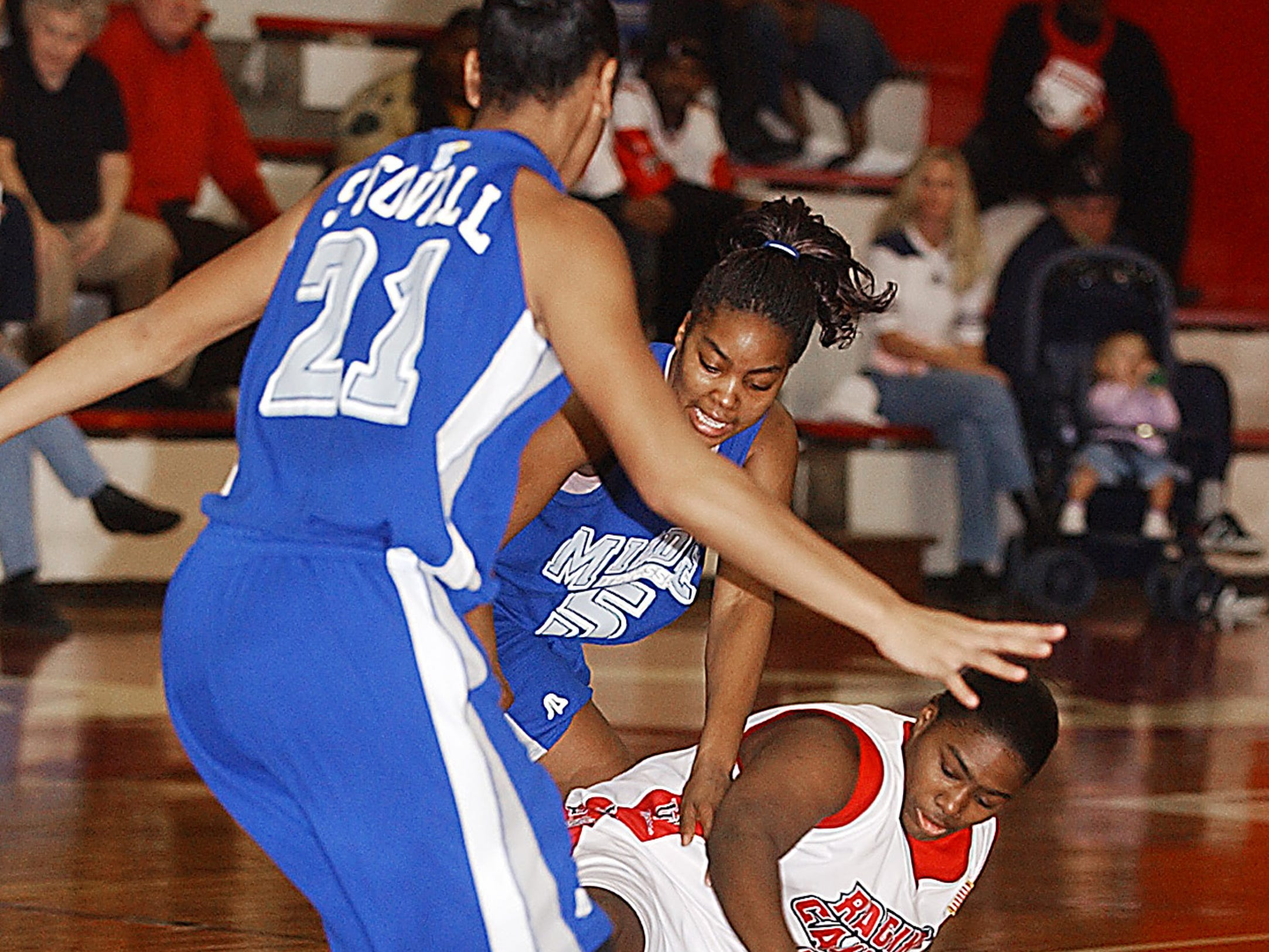 University of Louisiana senior Sharee Glenn struggles for control of a loose ball against Middle Tennessee's Tia Stovall, left, and Keisha McClinic during the match up between the two schools at the Earl K. Long.