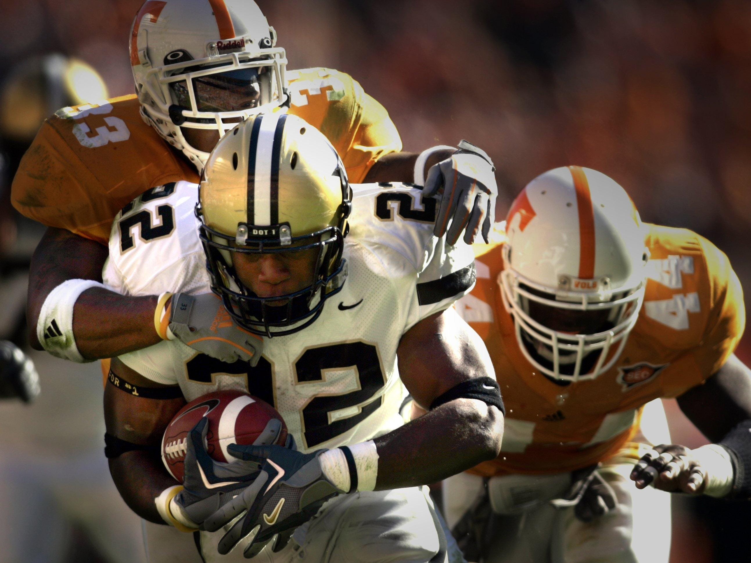 Vanderbilt's Cassen Jackson-Garrison (22) takes Jonathan Hefney (33) along for the ride as he picks up yardage while Tennessee plays Vanderbilt at Neyland Stadium in Knoxville on Nov. 19, 2005.