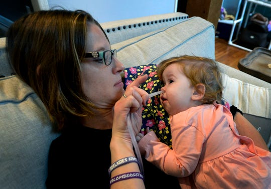 Rondi Kauffmann uses a suction tube to remove congestion and fluids from the nose and mouth of her daughter Adelaide on Tuesday, Nov. 13, 2018, in Burns, Tenn.