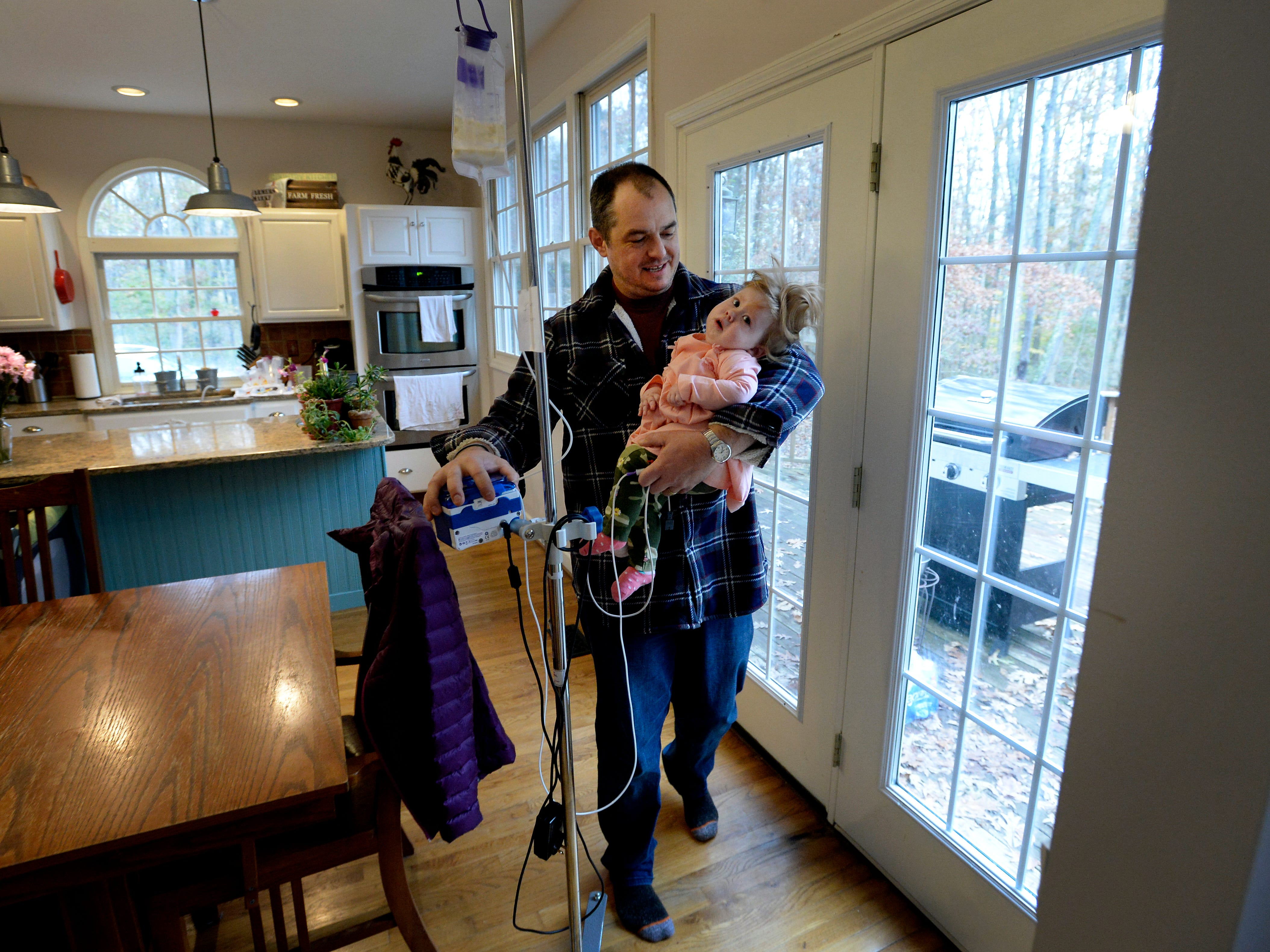 Adam Kauffmann walks with his daughter Adelaide and her monitor on Tuesday, Nov. 13, 2018, in Burns, Tenn.