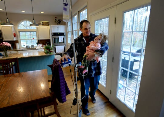 Adam Kauffmann walks with his daughter Adelaide and her monitor on  Nov. 13 in Burns, Tennessee.