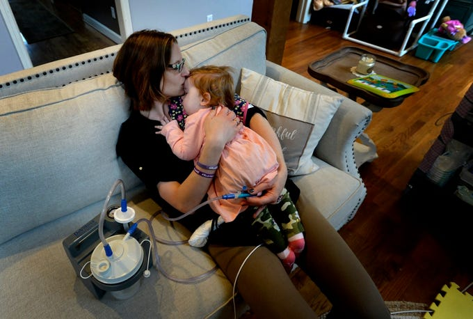 Rondi Kauffmann holds her daughter Adelaide Kauffmann as the baby falls asleep after a physical therapy session to improve her motor skills on Tuesday, Nov. 13, 2018, in Burns, Tenn. Adelaide has Spinal Muscular Atrophy - Type 1, which causes progressive weakening of her motor functions. Her parents make too much money to get Medicaid benefits, but cannot afford the $150,000 annual cost of a night nurse to care for Adelaide when she sleeps.
