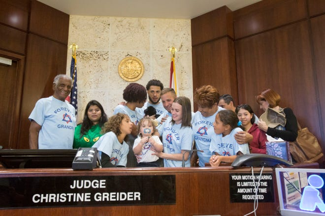 The Lorenso-Cata family stands for a photo in Judge Christine Greider's courtroom during National Adoption Day on Friday Nov. 16. Aloima Cata and her husband adopted 1-year-old Renzo Sander Lorenso into their large family.