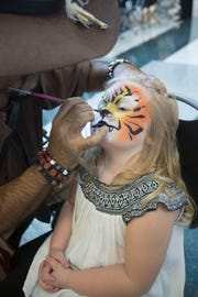 Aleeah Hedrich, 3, has her face painted by Miguel Bey. Hedrich was adopted Friday afternoon during a National Adoption day ceremony at the Collier County Courthouse.