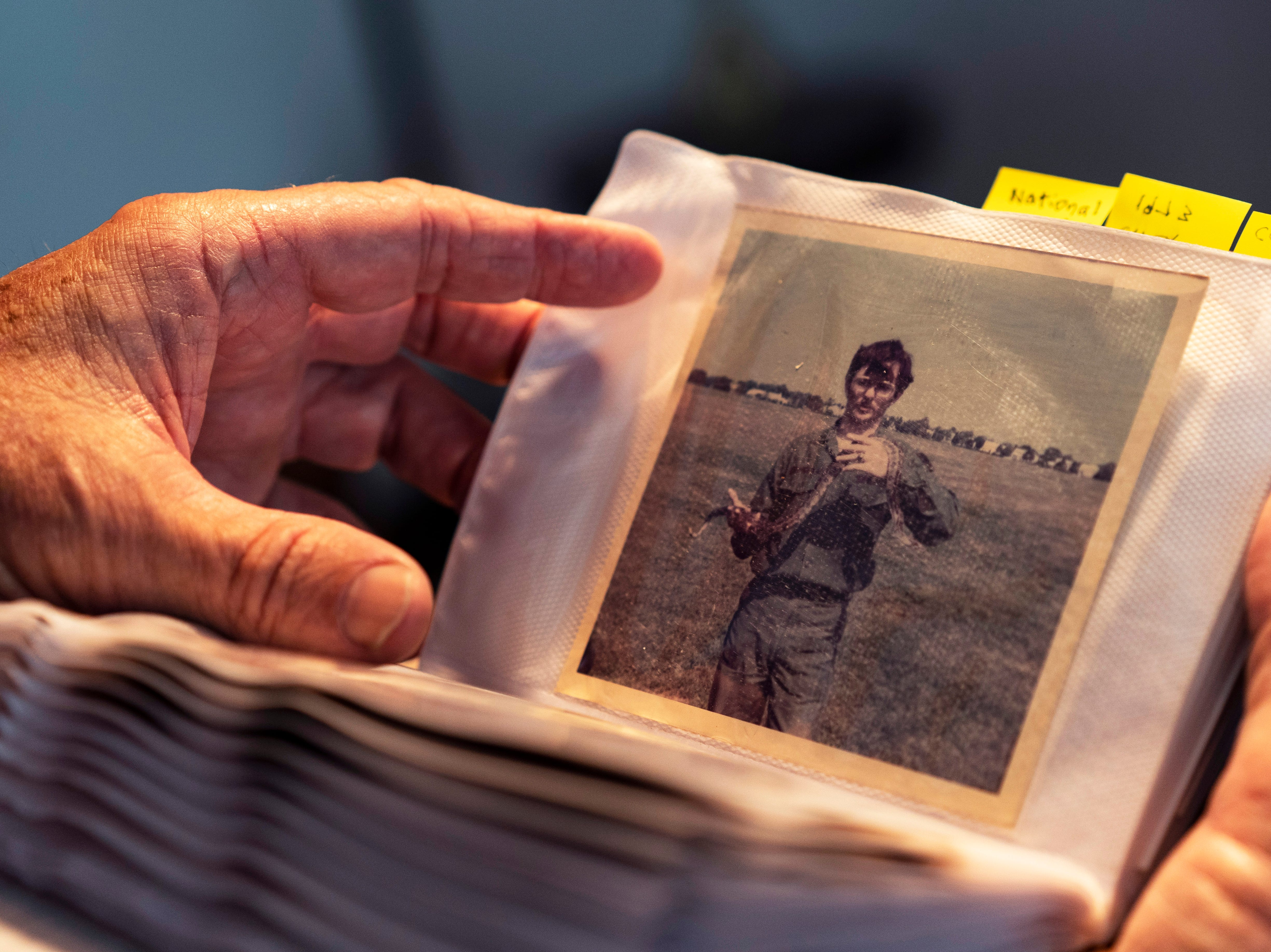 While arranging photographs, Dave Cornelisse takes a moment to look at a photo of him holding a snake while on National Guard duty. During the Vietnam War, Cornelisse spent six years in the National Guard, mostly as a driver.