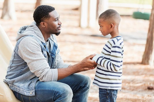 Father Talking To Little Boy On Playground