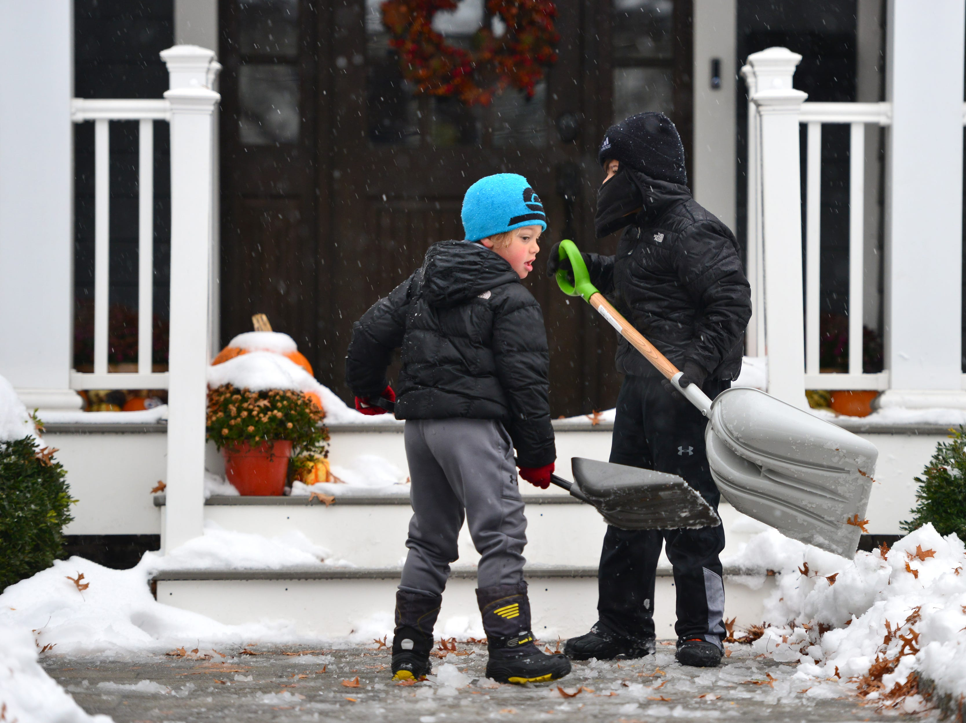 From left, Leo Mazza, 5, and his brother Luca, 8, help shovel the front walkway of their home as the snow and sleet falls in Hasbrouck Heights on Friday morning November 16, 2018.
