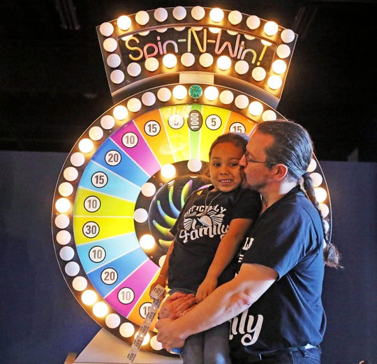 Matthew Pizzulli, of Clifton, kisses his adopted daughter, Bella, 4, at the arcade.