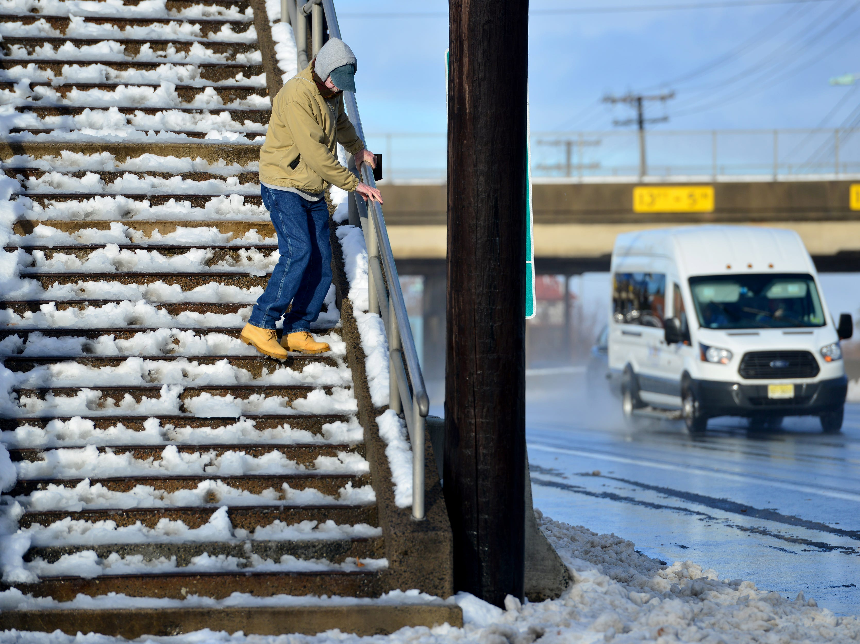 Bill Bragg, 69 of Fort Lee, holds tight onto the railing as he comes down an unshoveled stairs after crossing over Route 4 in Paramus on Friday morning November 16, 2018.