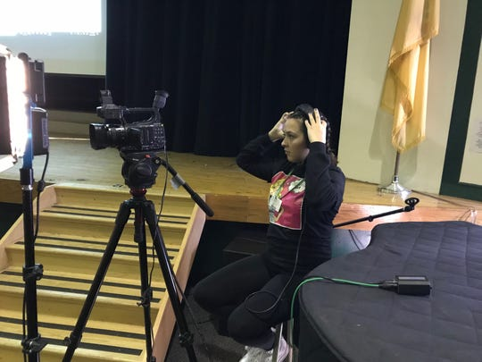 Passaic Valley High School student checks her mic with control booth as PV TV prepares to record Friday's signing ceremony with Montclair State University.