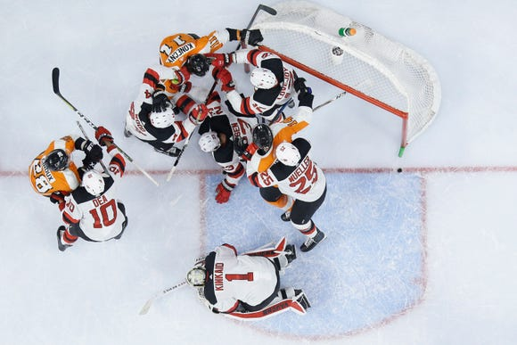 Philadelphia Flyers' players battle with New Jersey Devils' players after a save by Keith Kinkaid (1) during the second period of an NHL hockey game, Thursday, Nov. 15, 2018, in Philadelphia.