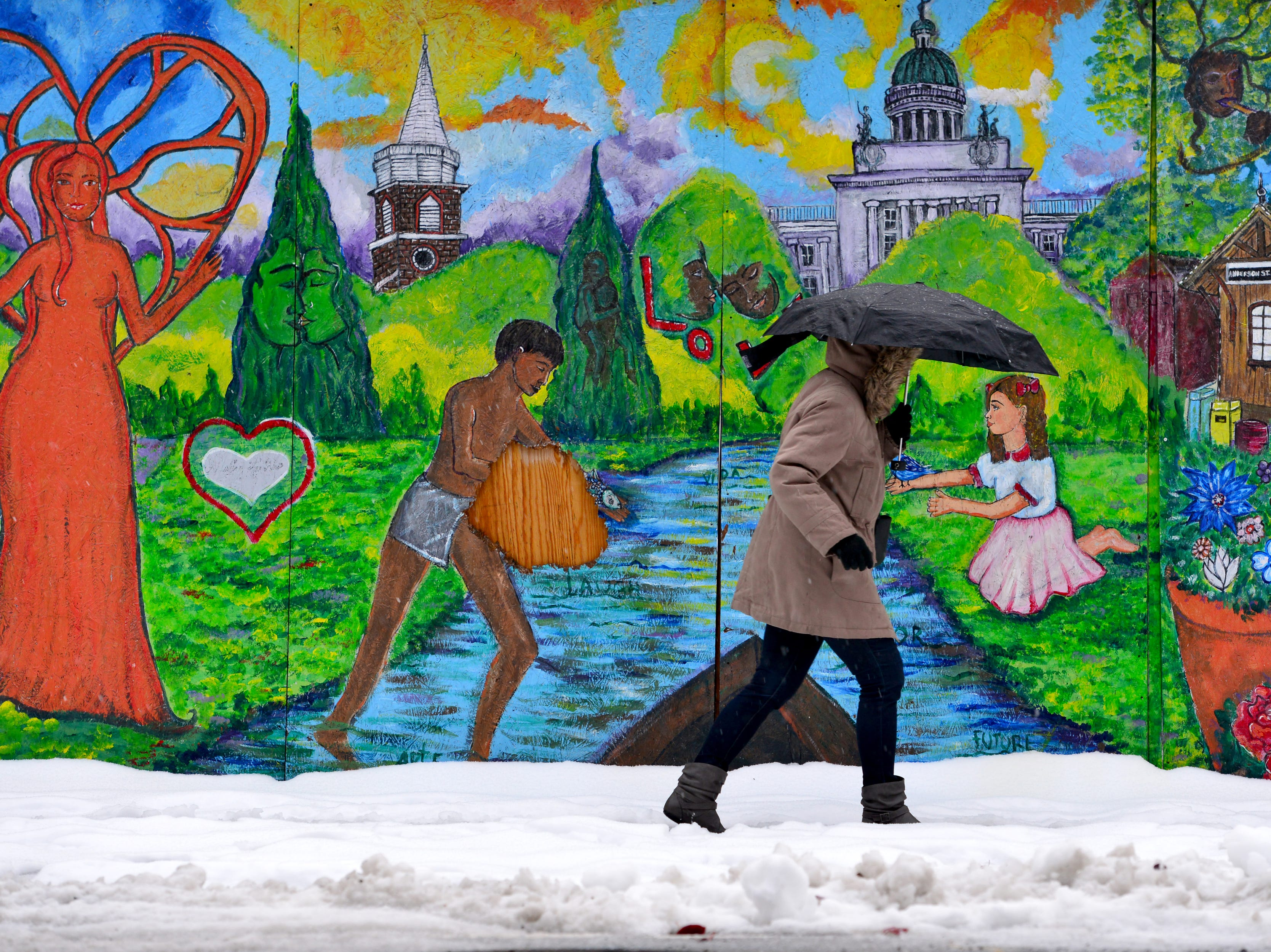 A woman with an umbrella to shied herself from the snow and sleet as she walks past a mural on Main St in Hackensack on Friday morning November 16, 2018.