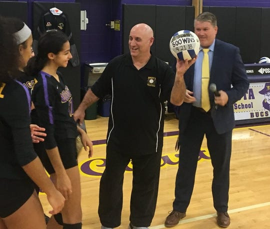 Bogota girls volleyball coach Brad DiRupo with the game ball from his 500th career win, after superintendent Damien Kennedy (right) made the formal presentation on Nov. 7, 2018.