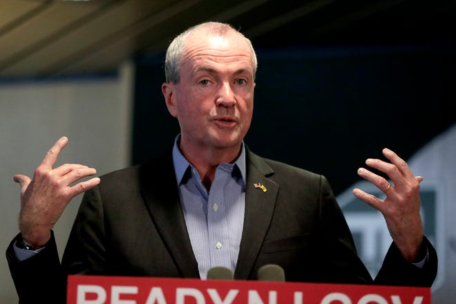 New Jersey Gov. Phil Murphy, center, speaks during a news conference addressing a snowstorm that hit the northern New Jersey region a day earlier, Friday, Nov. 16, 2018, in Woodbridge, N.J. Murphy is under fire because many commuters were stranded on highways during the snowstorm that hit during the rush hour traffic.