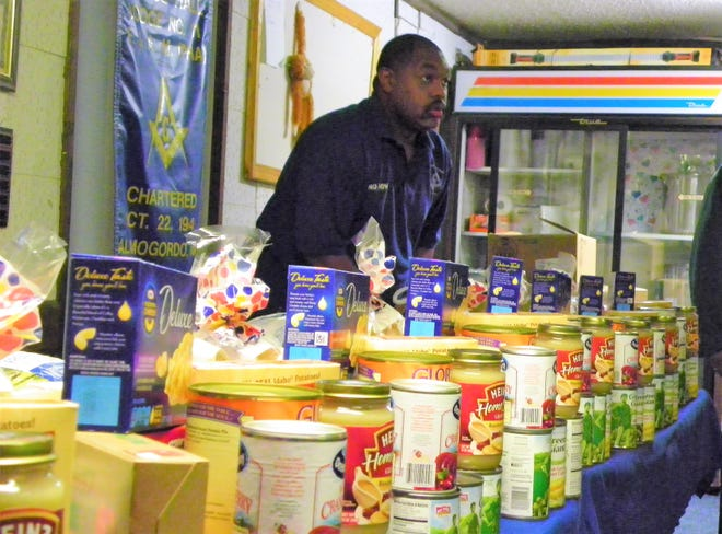 Prince Hall Lodge #11 F&AM member Everette Brown helps organize the components for the Thanksgiving meals that the group delivered to families in the community.