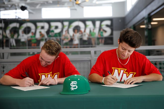 Farmington's Danny Carpenter, left, and Joseph Mihelich sign their letters of intent on Friday to continue their baseball careers at New Mexico Junior College.