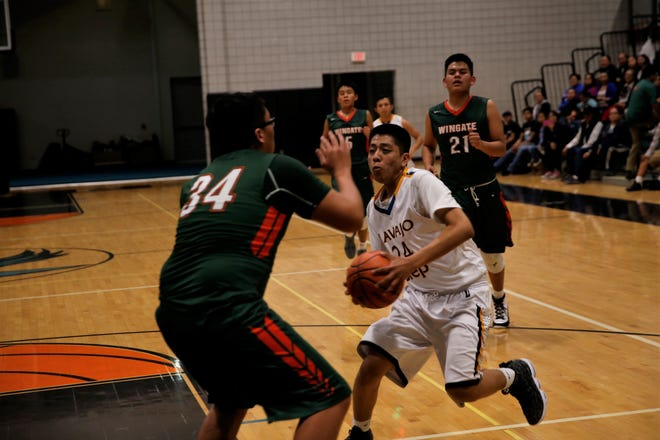Navajo Prep's Treston Yazzie charges toward the basket and encounters Wingate's Marvin Moses during a district boys basketball game on Feb. 6 at the Eagles Nest in Farmington. Prep opens the new season at the Jerry Richardson Memorial tournament on Nov. 29 in Shiprock.
