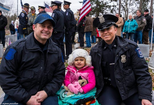 Novi Police Officer Shawn Penzak with his wife Hailey, also a Novi Police officer, with their daughter Avery, 2, at the funeral for police dog Moose.