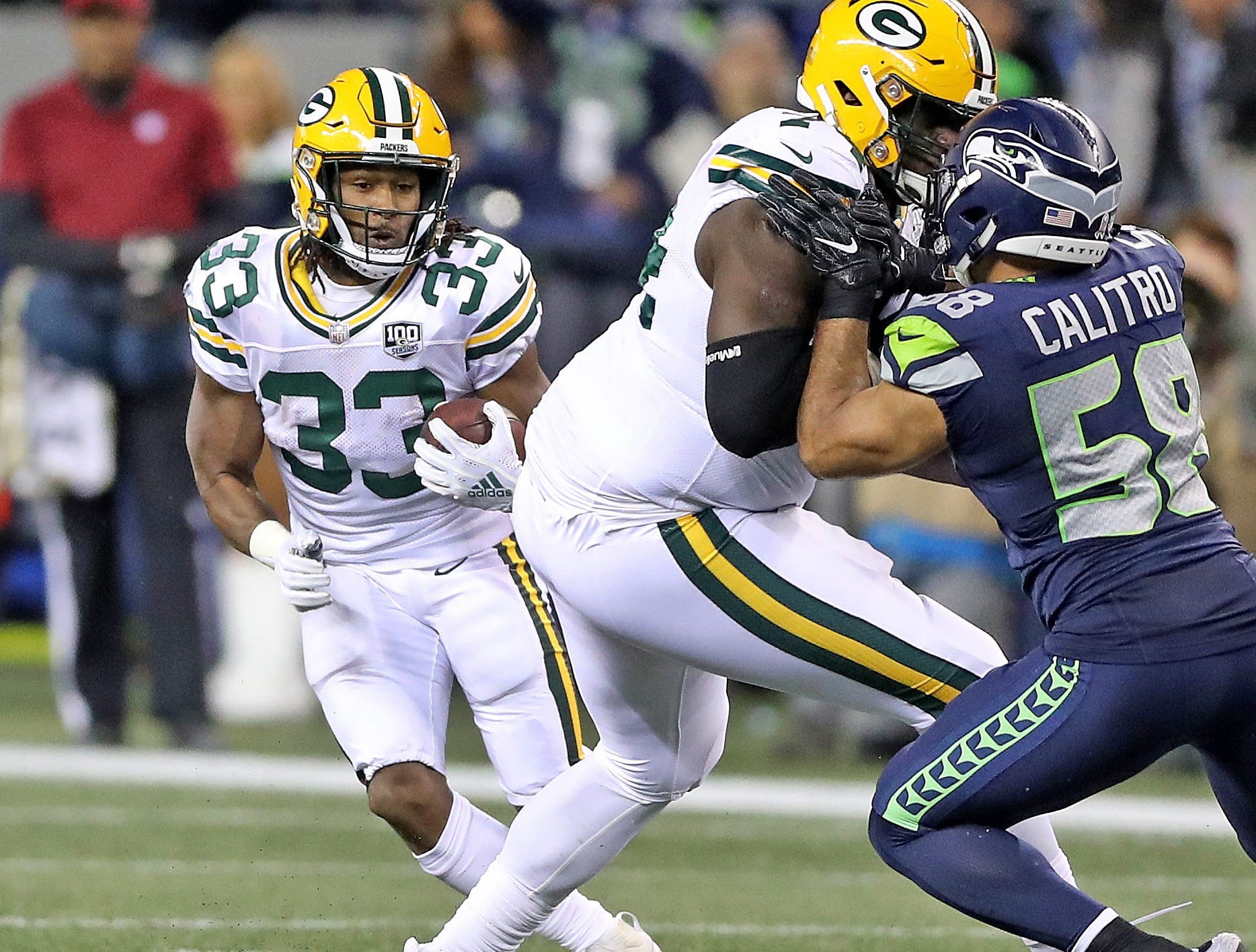 Green Bay Packers running back Aaron Jones (33) cuts behind the block of offensive guard Byron Bell (74) on outside linebacker Austin Calitro (58) on a screen pass against the Seattle Seahawks at CenturyLink Field Thursday, November 15, 2018 in Seattle, WA. Jim Matthews/USA TODAY NETWORK-Wis