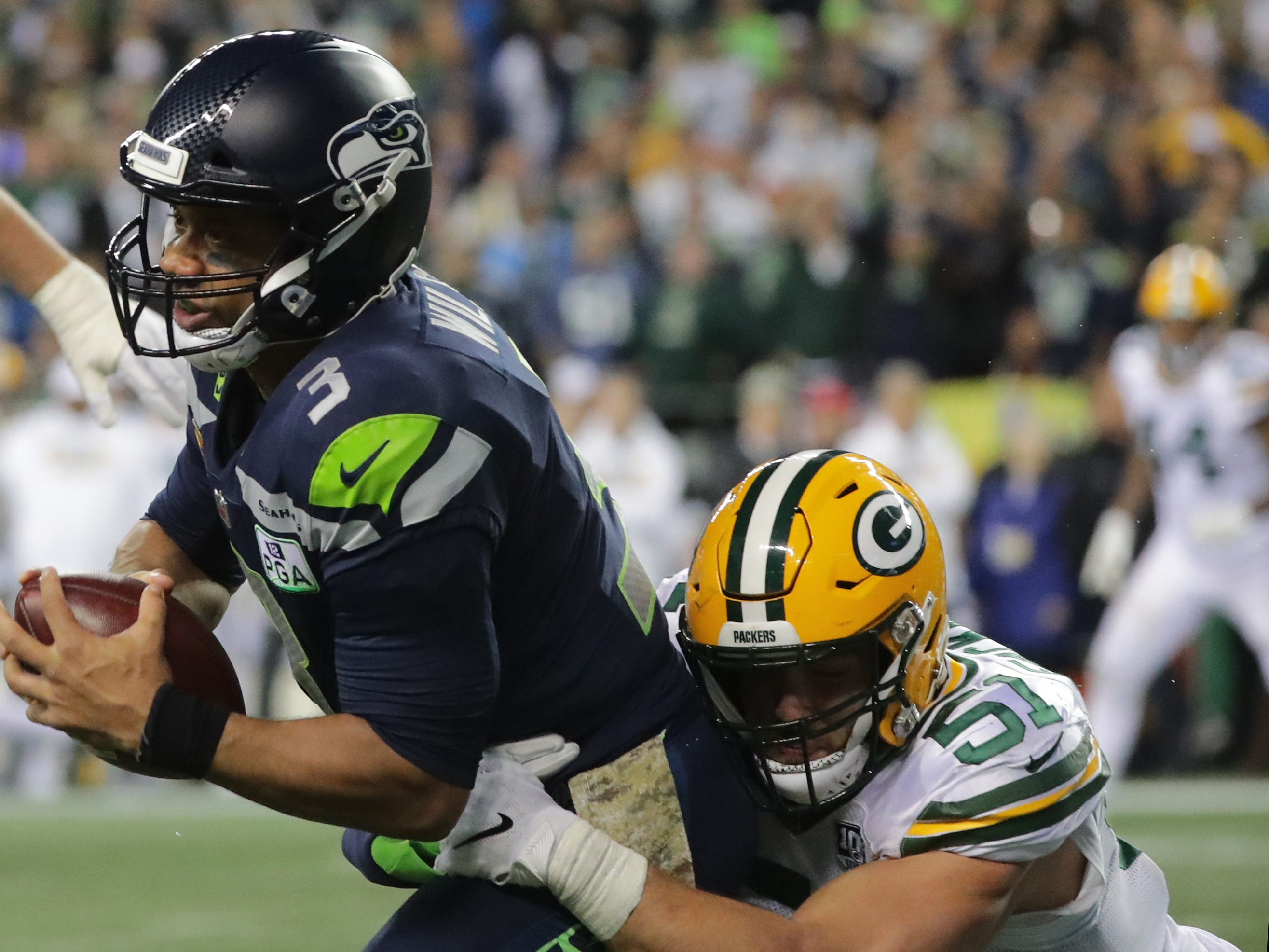 Seattle Seahawks quarterback Russell Wilson (3) manages to throw away the ball to avoid a sack by Green Bay Packers linebacker Kyler Fackrell (51) during the third  quarter of their game Thursday, November 25, 2018 at CenturyLink Field in Seattle, Wash.
