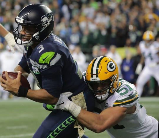 Seattle Seahawks quarterback Russell Wilson (3) manages to throw away the ball to avoid a sack by Green Bay Packers linebacker Kyler Fackrell (51) during the third  quarter of their game Thursday, Nov. 25, 2018 at CenturyLink Field in Seattle, Washington.