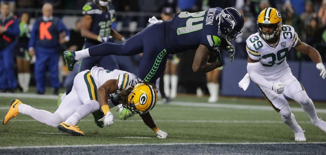 Seattle Seahawks tight end Ed Dickson (84) scores a touchdown on a 15-yard reception despite the efforts of Green Bay Packers cornerback Tramon Williams (38) during the fourth quarter of their game Thursday, November 25, 2018 at CenturyLink Field in Seattle, Wash.  MARK HOFFMAN/MHOFFMAN@JOURNALSENTINEL.COM