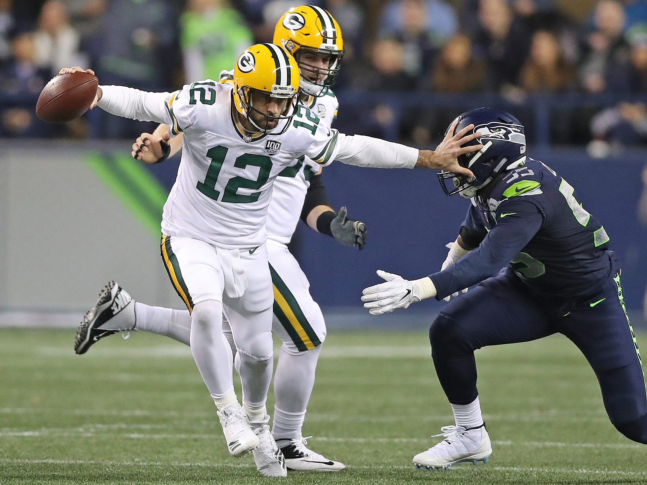 Green Bay Packers quarterback Aaron Rodgers (12) fends off a tackler against the Seattle Seahawks at CenturyLink Field Thursday, November 15, 2018 in Seattle, WA. Jim Matthews/USA TODAY NETWORK-Wis