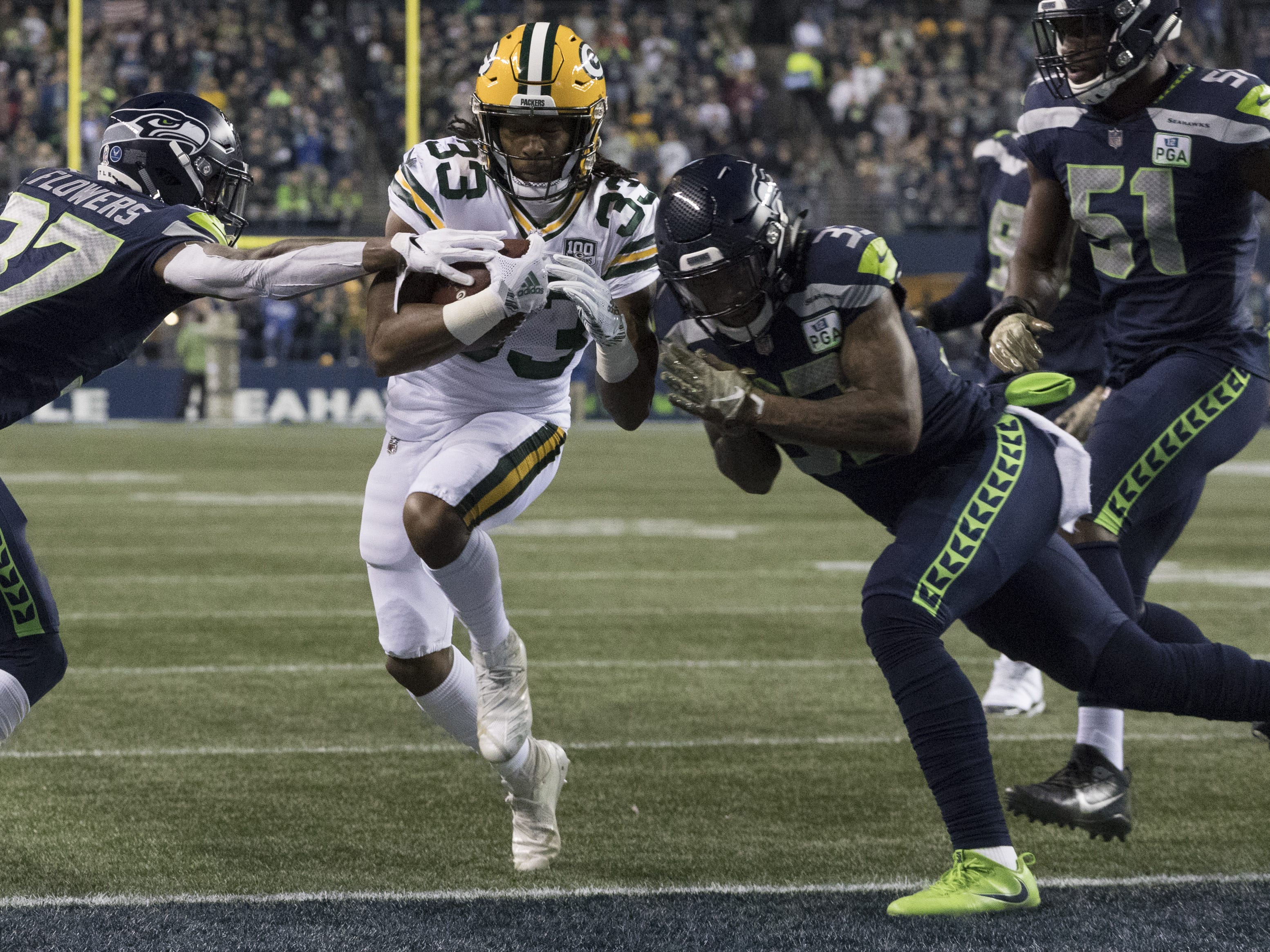 Green Bay Packers running back Aaron Jones (33) scores a touchdown on an eight yard run during the first quarter of their game against the Seattle Seahawks Thursday, November 25, 2018 at CenturyLink Field in Seattle, Wash.