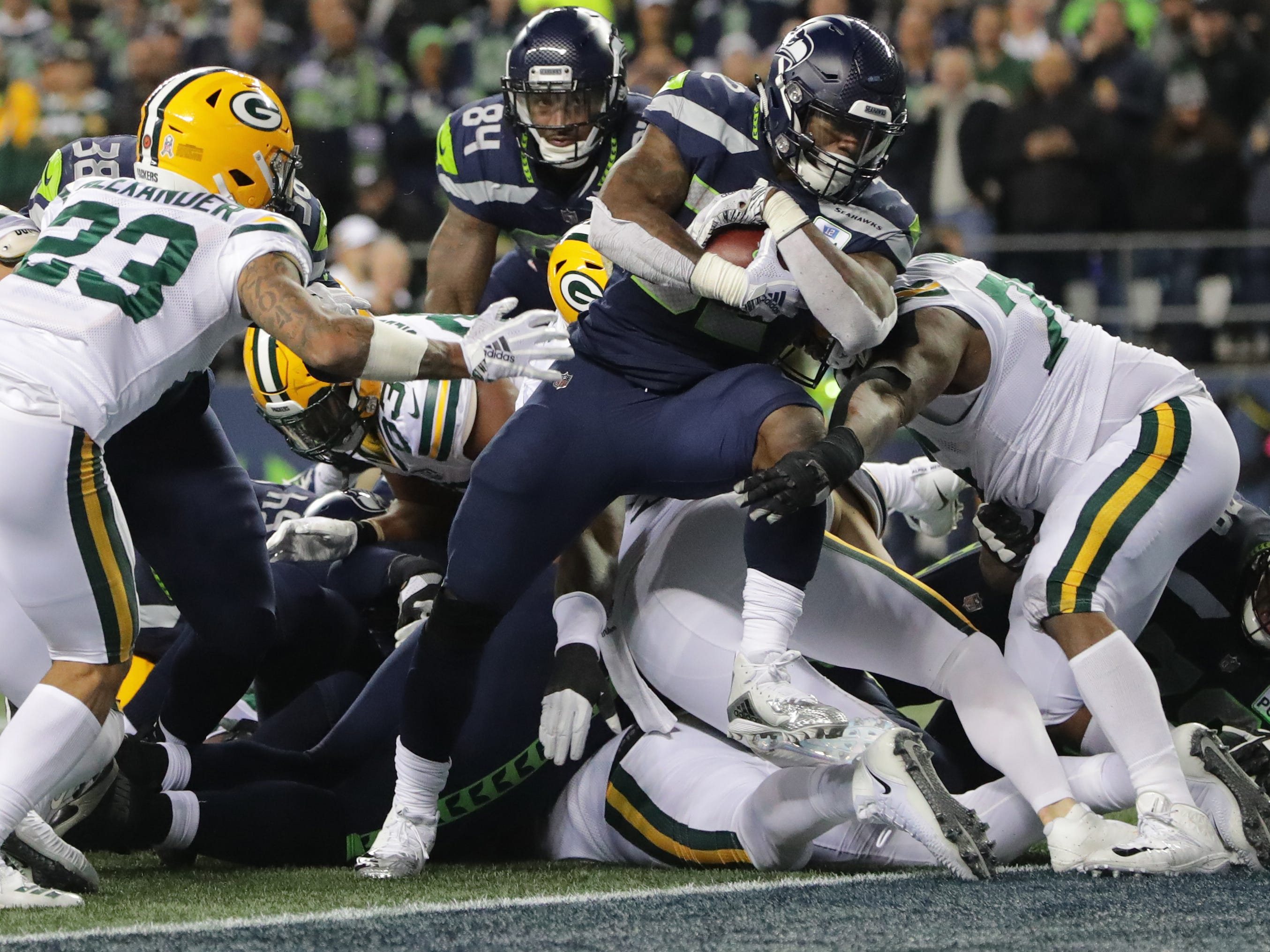 Seattle Seahawks running back Chris Carson (32) scores a touchdown on a one-yard run during the second quarter of their game against the Green Bay Packers Thursday, November 25, 2018 at CenturyLink Field in Seattle, Wash.  MARK HOFFMAN/MHOFFMAN@JOURNALSENTINEL.COM